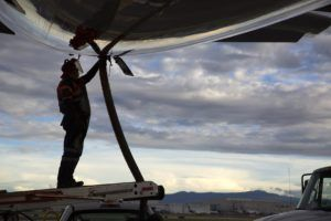 Airport staff operator refueling aircraft against blue sky