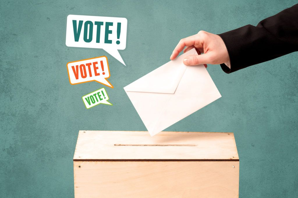 Presidential Cycle - A hand placing a voting slip into a ballot box